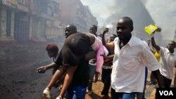 Para demonstran Uganda membawa seorang demonstran perempuan yang terluka akibat tembakan pasukan keamanan (29/4).