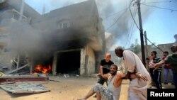 Cư dân Palestine đỡ một người bị thương vì pháo kích của Israel.