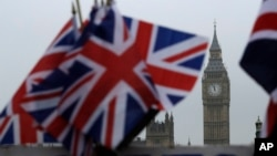 FILE - Union flags are displayed on a tourist stall, backdropped by the Houses of Parliament and Elizabeth Tower containing the bell known as Big Ben, in London, Feb. 8, 2017.