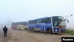 2017年4月14日,一名男子走近运载着从叙利亚卡夫拉亚和富阿镇疏散民众的巴士。