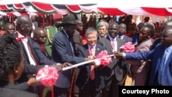 President Salva Kiir (center, with hat) and Japanese Ambassador to Juba Takeshi Akamatsu cut the ribbon at the groundbreaking in Juba to build a new bridge over the Nile.