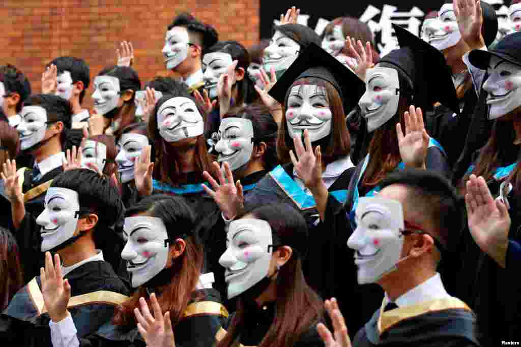 University students wearing Guy Fawkes masks pose for a photoshoot of a graduation ceremony to support anti-government protests at the Hong Kong Polytechnic University, Oct. 30, 2019.