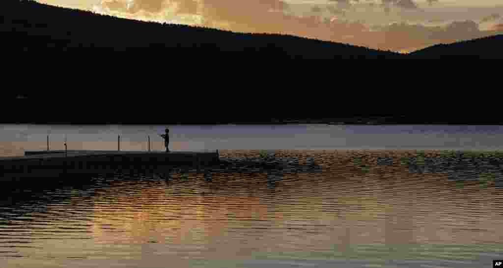 ماهیگیری یک پسر بچه به هنگام غروب آفتاب در کنار دریاچه ای در نیو مکزیکو