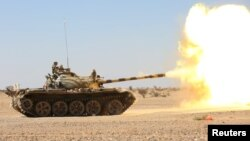 A tank operated by the government army fires at Houthi positions in the al-Labanat area, between Yemen's northern provinces of al-Jawf and Marib, Dec. 5, 2015.