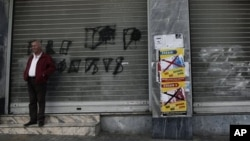 "A man stands outside a shuttered shop next a poster that reads ""Yes to Work, No to the Euro,"" Athens, Nov. 12, 2012."