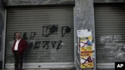 """Atina'da kapanan bir dükkanda""""işe evet, euro'ya hayır"""" yazısı"""