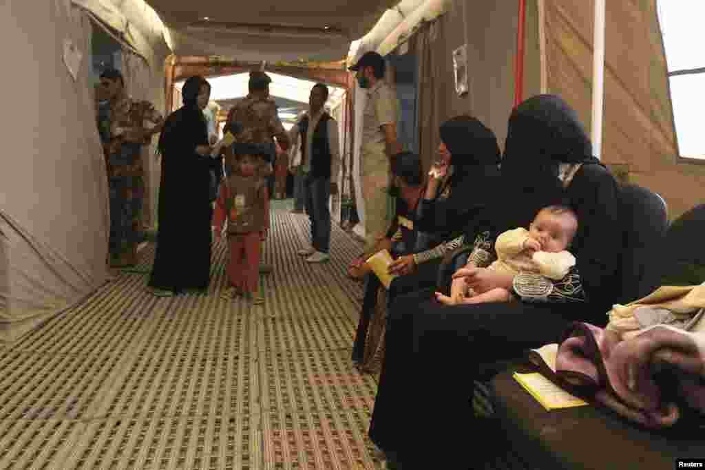 Syrian refugees wait for treatment at an Italian military hospital at the Al Zaatri refugee camp in the Jordanian city of Mafraq, near the Syrian border, June 25, 2013.