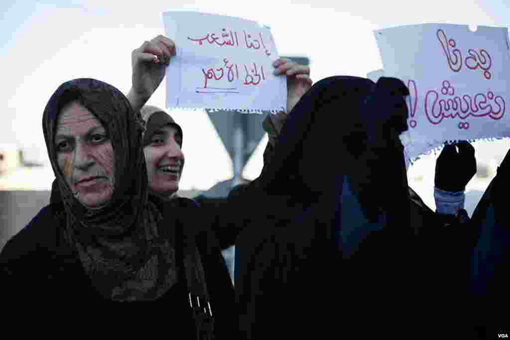 Protesters held up signs on the edge of Interior Ministry Circle in Amman. (Y. Weeks for VOA)