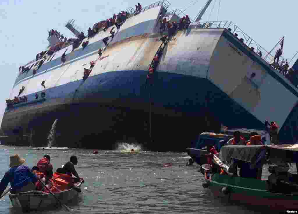 Passengers climb down the side of the ferry KM Wihan Sejahtera as it capsizes in Tanjung Perak port, Surabaya, East Java in this photo provided by Antara Foto.