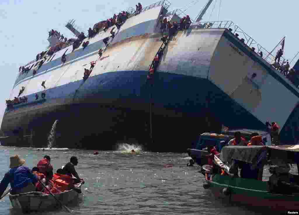 អ្នកដំណើរចុះពីនាវាឈ្មោះ KM Wihan Sejahtera ខណៈដែលនាវានេះក្រឡាប់នៅផែ Tanjung Perak ក្នុងក្រុង Surabaya ភាគខាងកើតនៃកោះជ្វា នៅក្នុងរូបថតដែលផ្តល់ដោយ Antara Foto។