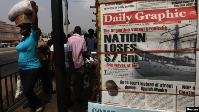 People walk past a vendor selling newspapers with its front page reporting about an Argentine naval vessel involved in a debt dispute, in Accra, Ghana, December 2012.