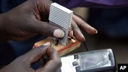 """Jeremiah Murimi, a Kenyan electrical engineering student demonstrates how a """"smart charger"""" connected to a bicycle can power a mobile phone (file photo)."""