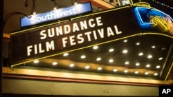 FILE - The Sundance Film Festival sign in lit up on Main Street, Park City, Utah.