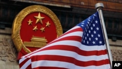 FILE - In this Nov. 9, 2017, file photo, an American flag is flown next to the Chinese national emblem during a welcome ceremony for visiting U.S. President Donald Trump outside the Great Hall of the People in Beijing.