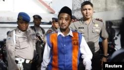 Pemimpin kelompok Syiah di Madura, Tajul Muluk, dikawal polisi di Pengadilan Negeri Sampang. (Photo: REUTERS/Sigit Pamungkas).