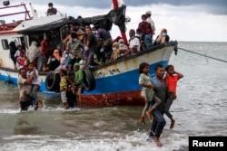 Warga Aceh membantu para pengungsi Rohingya turun dari kapal mereka di pantai Aceh utara (foto: Antara/Rahmad/ via REUTERS).
