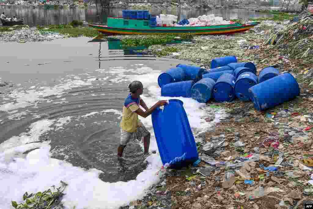 Ishchi kimyoviy moddalar saqlangan idishlarni daryoda yuvmoqda. Bangladesh.