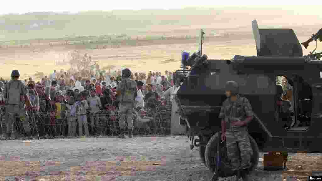 Turkish Deputy Prime Minister Numan Kurtulmus told CNN Turk television on Saturday that 45,000 Syrian Kurds had crossed the border since Turkish authorities opened it on Friday. Earlier this week, Turkish soldiers stand guard as Syrians wait behind the bo