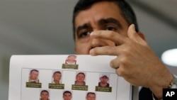 El ministro de Relaciones Interiores y Justicia de Venezuela, Miguel Rodríguez Torres, muestra fotos de los presuntos complotados.