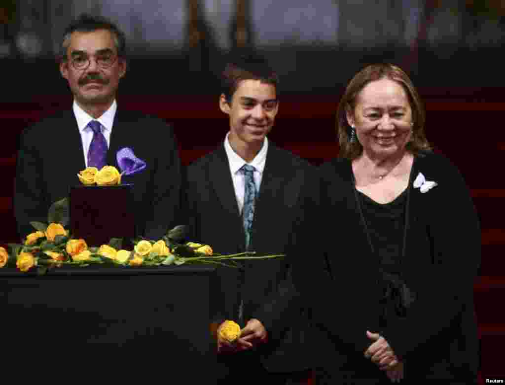 Mercedes Barcha (right), widow of late Colombian Nobel laureate Gabriel Garcia Marquez, her son Gonzalo Garcia Barcha (left), and her grandson stand next to an urn containing Garcia Marquez's ashes for public viewing in the Palace of Fine Arts in Mexico City, April 21, 2014.