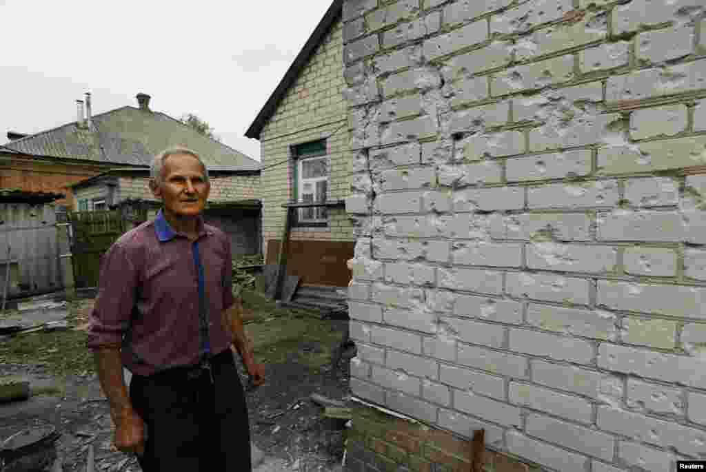 Yevgeni Kharkovski, 75, surveys the damage caused to his home by mortar shelling two nights ago, Slovyansk, Ukraine, May 12, 2014.