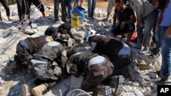 This photo provided by the Syrian Civil Defense White Helmets shows civil defense workers searching in the rubble after airstrikes hit in Khan Sheikhoun, in the northern province of Idlib, Syria, Sept, 24, 2017.