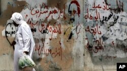 FILE - A man walks past graffiti on a wall portraying opposition activist Ibrahim Sharif, in the western village of Malkiya, Bahrain.