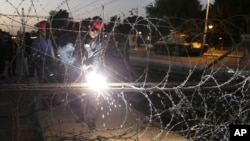Egyptian Army soldiers install barbed wire outside the presidential palace to secure the site of overnight clashes between supporters and opponents of President Mohammed Morsi in Cairo, Egypt, Thursday, Dec. 6, 2012.