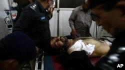 Sĩ quan cảnh sát Pakistan bên cạnh một đồng nghiệp bị thương tại một bệnh viện địa phương ở Peshawar, Pakistan, ngày 10/4/2013.