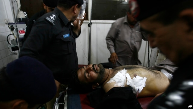 Pakistani police officers surround their injured colleague at a local hospital in Peshawar, Pakistan, April 10, 2013.