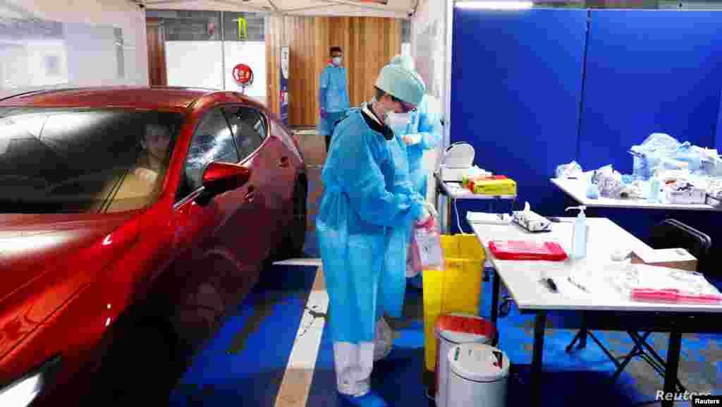 벨기에 리에주에서 신종 코로나바이러스 감염증(코로나19) 검사를 위한 '드라이브 인'(Drive In·차량 이동식) 선별 진료소가 문을 연 가운데 보호장비를 착용한 의료 관계자가 환자의 코에서 샘플을 채취한 후 봉지에 보관하고 있다.