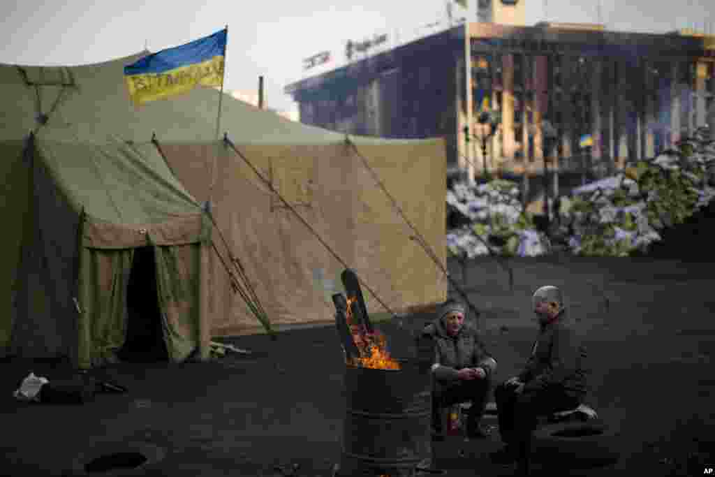 Opposition supporters warm themselves around a fire in Kyiv's Independence Square, Feb. 24, 2014.
