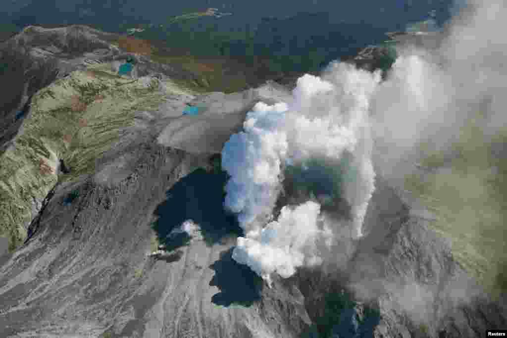 Asap vulkanik terlihat mengepuldari puncak gunung Ontake, yang terletak di antara wilayah Nagano dan Gifu di Jepang bagian tengah (29/9).