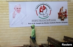 FILE - A boy is pictured below a banner of Pope Francis before a special mass at St. Joseph the Worker Catholic Parish where Pope Francis is expected to visit Kangemi, a slum that is home to 650,000 people in Kenya's capital Nairobi, Nov. 22, 2015.