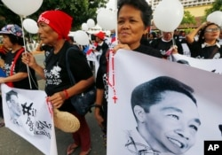 FILE - Supporters of the late Philippine dictator Ferdinand Marcos display his images prior to marching towards the Supreme Court for an overnight vigil, Nov. 7, 2016.