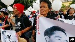 ບັນດາຜູ້ສະໜັບສະໜູນມື້ລາງຈອມຜະເດັດການ Ferdinand Marcos ສະແດງຮູບພາບຂອງທ່ານ.