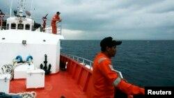 Thành viên của đội cứu hộ đứng trên boong tàu cứu hộ Basarnas trong nhiệm vụ tìm kiếm chiếc máy bay Malaysia bị mất tích trong vùng biển Andaman.