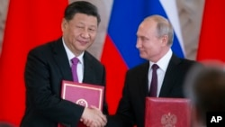 2019年6月5日俄罗斯总统普京和中国国家主席习近平在俄罗斯莫斯科克里姆林宫举行会谈后的签字仪式上交换文件