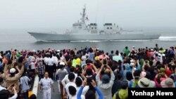 한국 해군작전사령부가 22일 마련한 '제63주년 대한해협 해전 전승기념 함정공개·항해체험' 행사에 참가한 시민들이 대형수송함 독도함을 타고 해상사열을 보고 있다.