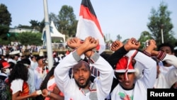 People show the Oromo Protest gesture as they chant anti-government slogans during Irreechaa Festival, the Oromo People thanksgiving ceremony at the Hora Finfinnee, in Addis Ababa, Ethiopia, Oct. 2, 2021.