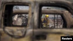 Un bombero visto a través de un auto destruido por las llamas en Middletown, California.