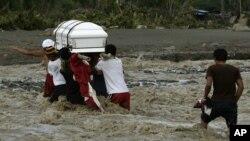 Thân nhân lội qua sông để chôn người thân thiệt mạng vì lũ lụt ở thị trấn New Bataan, miền nam Philippines, ngày 6/12/2012.
