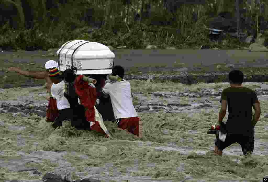 Relatives cross a river to bury their loved one, who died in a flash flood caused by Typhoon Bopha in New Bataan township, Compostela Valley, Philippines, December 6, 2012.