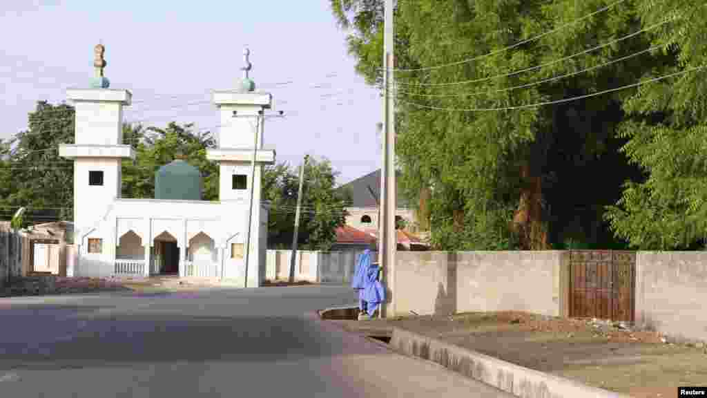 Two children walk in an empty street as they make their way home in the city of Maiduguri, Borno State May 19, 2013.