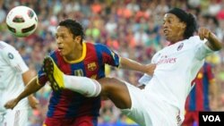 Pemain Barcelona Adriano Correia berebut bola dengan pemain AC Milan Ronaldinho dalam pertandingan persahabatan di Barcelona, 25 Agustus 2010. Meningkatnya ancaman akan pengaturan hasil pertandingan dikawatirkan oleh UEFA merusak integritas sepakbola di E