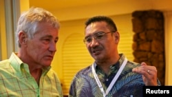 U.S. Secretary of Defense Chuck Hagel (L) listens to Malaysian Defense Minister and acting Transport Minister Hishammuddin Hussein during a welcome reception for Southeast Asian defense ministers in Honolulu, Hawaii, April 1, 2014.
