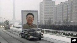 រថយន្តលីមូហ្ស៊ីនដែលដឹករូបថតសពអតីតមេដឹកនាំកូរ៉េខាងជើង គីម ជុងអ៊ីល (Kim Jong-il) មួយនេះនាំមុខក្បួនរថយន្តនៃពិធីបុណ្យសព កាត់តាមដងវិថីទីក្រុងព្យុងយ៉ាង ដែលមានមនុស្សនៅអមសងខាងយ៉ាងកកកុញ។
