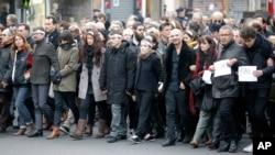 Nhân viên báo Charlie Hebdo, với họa sĩ vẽ tranh biếm họa Renald Luzier, xuống đường tuần hành với thân nhân của các nạn nhân thiệt mạng trong vụ tấn công siêu thị Kosher ở Paris, ngày 11/1/2015.