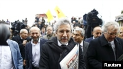 Cumhuriyet editor-in-chief Can Dundar, center, arrives at the Justice Palace in Istanbul, Turkey, March 25, 2016.