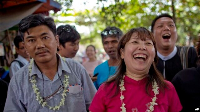 Myanmar civic rights activists Soe Moe Tun (l) and Ma Tandar, both wearing flower- garlands, laugh outside prison after receiving a presidential pardon in the suburbs of Yangon, Myanmar,  Dec. 11, 2013.